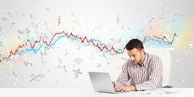 Business man sitting at table with stock market graph 3d letters-729584-edited.jpeg