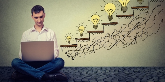 Happy young man entrepreneur working on computer sitting on a floor in his office successful in increasing internet website traffic. Promotion, company growth concept. Isolated on gray wall background-093350-edited.jpeg