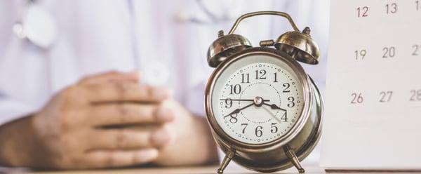 zegar i kalendarz na biurku czekającego na coś lekarza